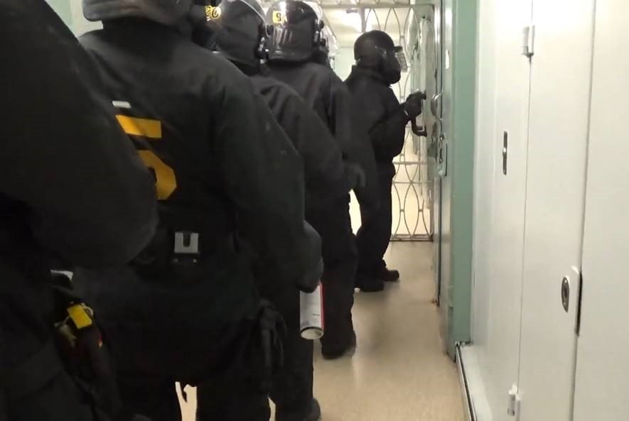 Photo of an Emergency Response Team lined up at the door of a cell at Atlantic Institution