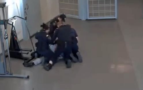 Photo of an inmate lying prone on the floor with four officers on top of him